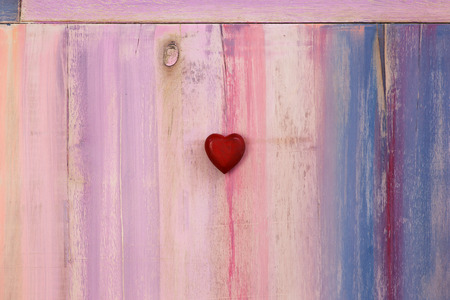 Love message space on colorful painted board with red wooden heart and copy space photo