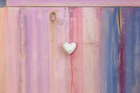 Love message space on colorful painted board with white wooden heart and copy space photo