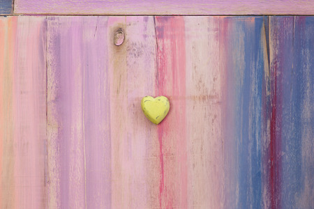 Love message space on colorful painted board with yellow wooden heart and copy space photo