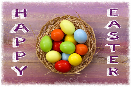 Happy easter text with painted eggs in wicker basket purple background white frame photo