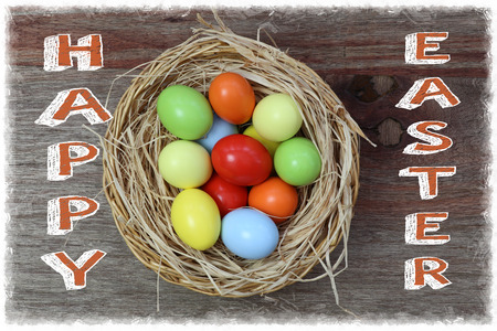 Happy easter text with painted eggs in wicker basket rough wood background white frame Stock Photo