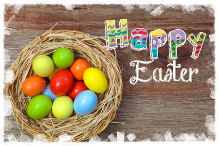 easter message: Happy easter text with painted eggs in wicker basket rough wood background white frame Stock Photo