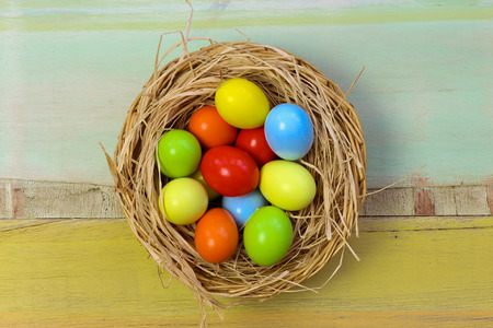 Happy easter text with painted eggs in wicker basket light green background copy space