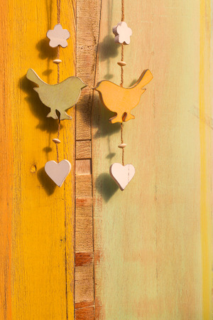 Hanging decor wooden birds, hearts and butterfly on strong over painted background photo