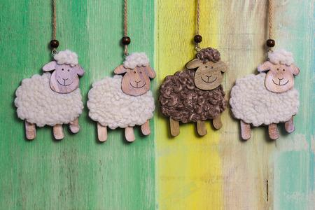 Handgemachte wei�e und schwarze Schafe auf gemalten Hintergrund