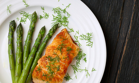 Salmon fillet with asparagus and dill on white plate dark rough wood Stock Photo