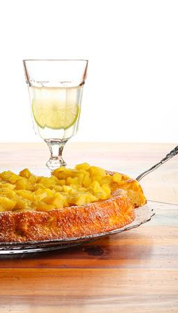 S��er Kuchen mit Rhabarber und �pfel auf Glasplatte Puderzucker, raue bemalten Holztisch, Limonade in Glas Lizenzfreie Bilder