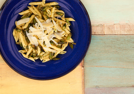 Pasta penne with asparagus and parmesan cheese on dark blue plate, painted background Stock Photo