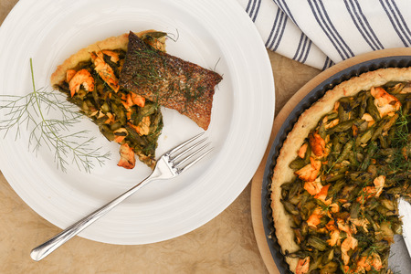 Asparagus zucchini salmon quiche with homemade shortcrust pastry and dill in backing tray with crispy salmon skin, shiny fork on white plate