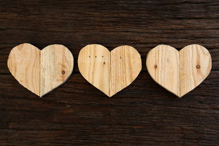 Love Valentines wooden hearts from recycled old palette on rough driftwood background, copy space photo