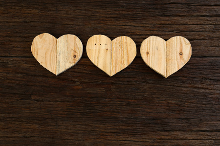 Love Valentines wooden hearts from recycled old palette on rough driftwood background, copy space