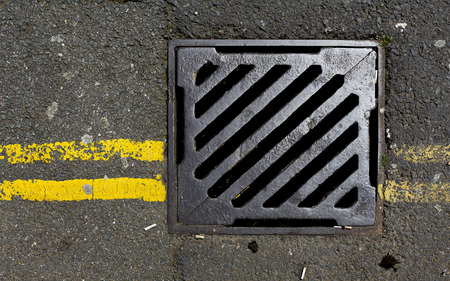 Road drains - sewer cover with double yellow lines photo