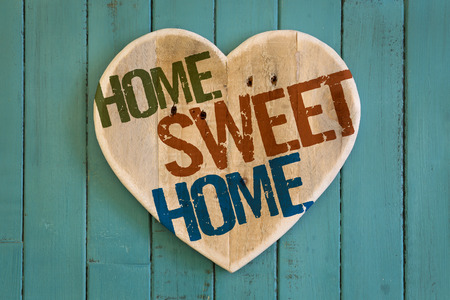 Home Sweet Home message wooden heart from recycled old palette on turquoise painted background, copy space Stock Photo