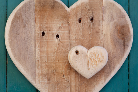 Love Valentines wooden heart from recycled old palette on turquoise painted background, copy space