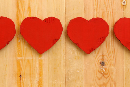 Love Valentines red painted recycled cardboard hearts on rough sawn pine boards background, copy space photo