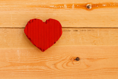 Love Valentines red painted recycled cardboard heart on rough sawn pine boards background, copy space photo