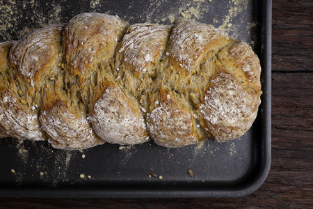fibber: Freshly baked traditional sunflower seed three strand bread plait on backing tray