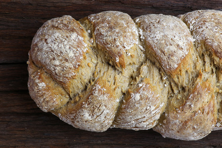 fibber: Freshly baked traditional sunflower seed three strand bread plait on dark wooden background Stock Photo
