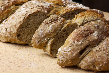 fibber: Freshly baked traditional sunflower seed three strand bread plait sliced on backing tray