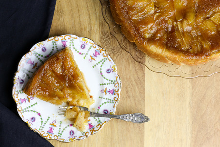 afternoon fancy cake: Caramelised apple tarte tart tartin fancy cake pie on glass plate slice cut off on saple table with serving plate