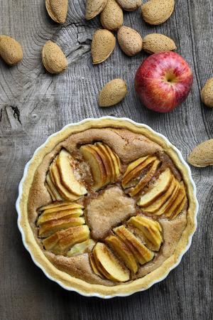 French apple tart sweet cake in white desert pie backing tray on old elm wooden table