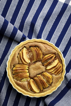 white backing: French apple tart sweet cake in white desert pie backing tray on blue striped cloth Stock Photo
