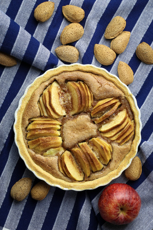 white backing: French apple tart sweet cake in white desert pie backing tray on blue striped cloth and whole almonds