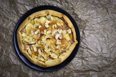 afternoon fancy cake: Apple galette crostata sweet cake pie on black desert plate on wrinkled backing paper