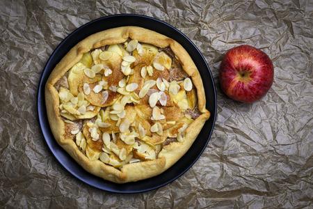 backing: Apple galette crostata sweet cake pie on black desert plate on wrinkled backing paper