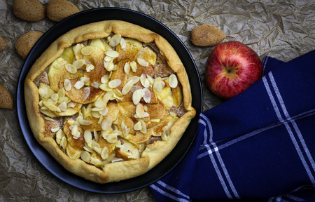 afternoon fancy cake: Apple galette crostata sweet cake pie on black desert plate on wrinkled backing paper with blue cloth and whole almonds Stock Photo