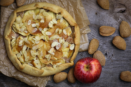 afternoon fancy cake: Apple galette crostata sweet cake pie on wrinkled backing paper and rough elm wood whole almonds Stock Photo