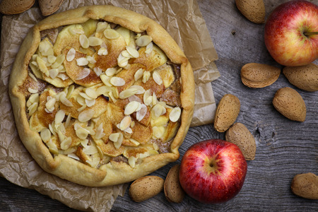 Apple galette crostata sweet cake pie on wrinkled backing paper and rough elm wood whole almonds Stock Photo