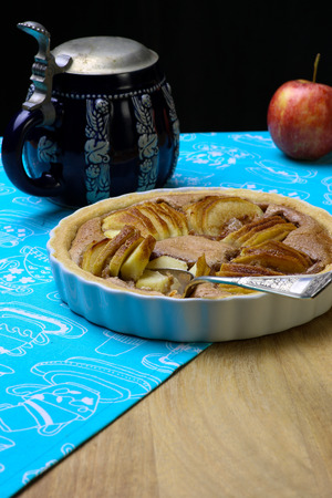 white backing: French apple tart sweet cake in white desert pie backing tray on bright blue cloth Stock Photo