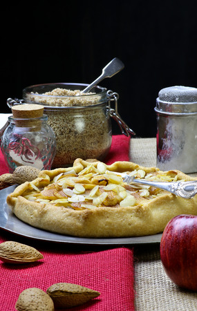 Apple galette crostata sweet cake pie on red and natural hessian fabric whole and crushed almonds icing sugar photo