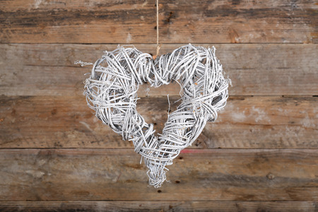 Heart shape white christmas wreath from natural painted twigs on old wooden rustic background photo