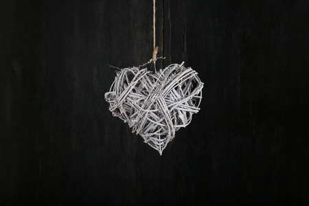 Heart shape white christmas wreath from natural painted twigs on old dark rustic background photo