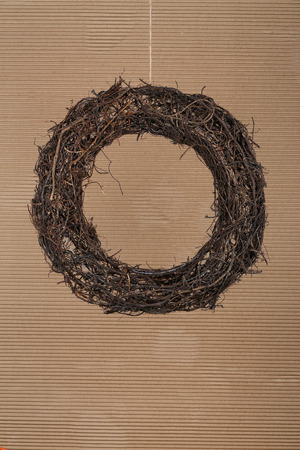 Round brown christmas wreath from natural twigs on old cardboard rustic background photo