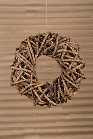 Round brown christmas wreath from natural twigs on old cardboard rustic background