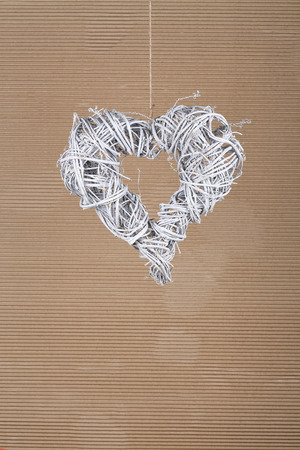 Heart shape white christmas wreath from natural painted twigs on old cardboard rustic background, copy space photo