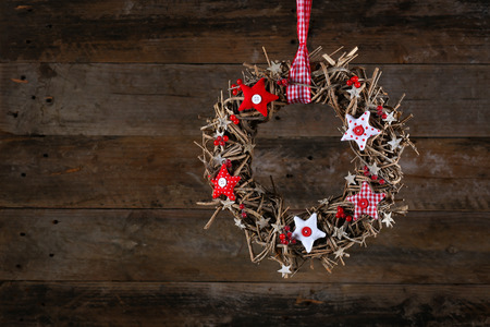 Decorated christmas wreath with red and white stars brown twigs gingham and polka dot on old wooden rustic background, copy space photo