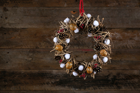 Decorated christmas wreath with walnuts, cotton buds, brown twigs and pine cones on old wooden rustic background, copy space photo