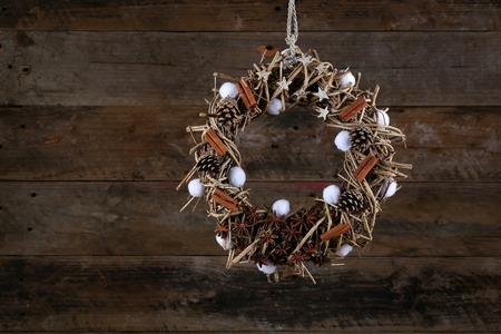 Decorated christmas wreath with cotton buds, pine cones, anise and cinnamon sticks on brown twigs,  old wooden rustic background, copy space photo