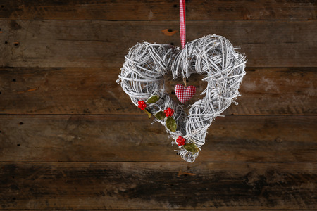 Decorated christmas wreath with gingham ribbon and heart, holly berries old wooden rustic background, copy space photo
