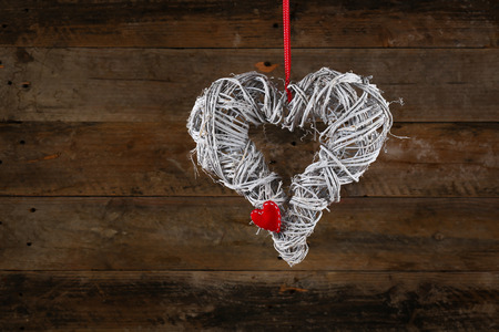 Decorated christmas wreath with gingham ribbon and red heart on old wooden rustic background, copy space