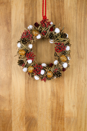 Decorated christmas wreath with red and white pillow hearts brown twigs walnuts and pine cones on sapele wood background, copy space photo