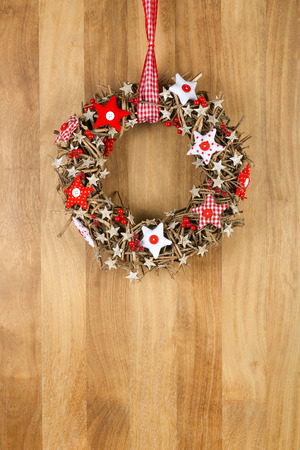 Decorated christmas door wreath with red and white pillow stars brown twigs gingham and polka dot on sapele wood background, copy space photo