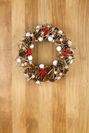 Decorated christmas door wreath with birch stars, cinnamon sticks, anise stars and pine cones brown twigs on sapele wood background, copy space photo