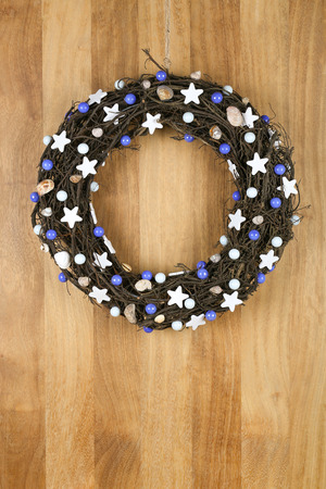 Decorated christmas door wreath with white stars and blue pearls brown twigs on sapele wood background, copy space photo