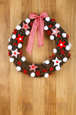 Decorated christmas door wreath with red and white pillow stars with gingham bow brown twigs gingham and polka dot on sapele wood background, copy space photo