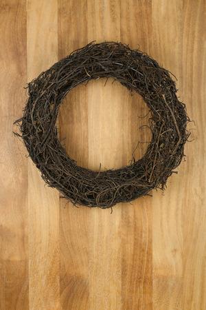 Christmas door wreath dark brown twigs on sapele wood background, copy space photo